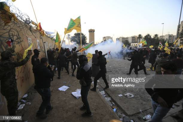US soldiers intervene in outraged Iraqi protesters as they storm the US Embassy in Baghdad protesting Washington's attacks on armed battalions belong...