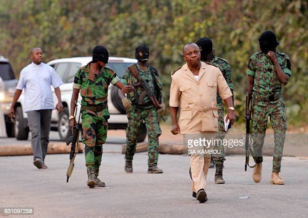 Soldiers involved in the mutiny walk with the sousprefet and a clergyman attempting to meet the mutineers in Bouake on January 6 2017 at the entrance...