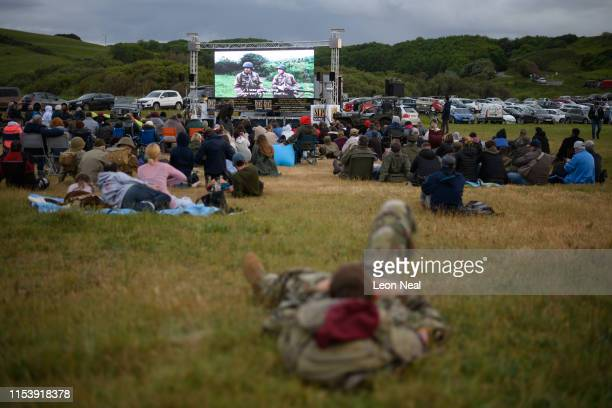 """Soldiers join visitors on Omaha Beach to watch an outdoor screening of the World War II film """"Saving Private Ryan"""" on June 05, 2019 in..."""
