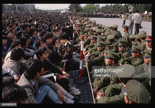 Soldiers keep student demonstrators away from the official memorial for Hu Yaobang at the Great Hall of the People where the service is being held...