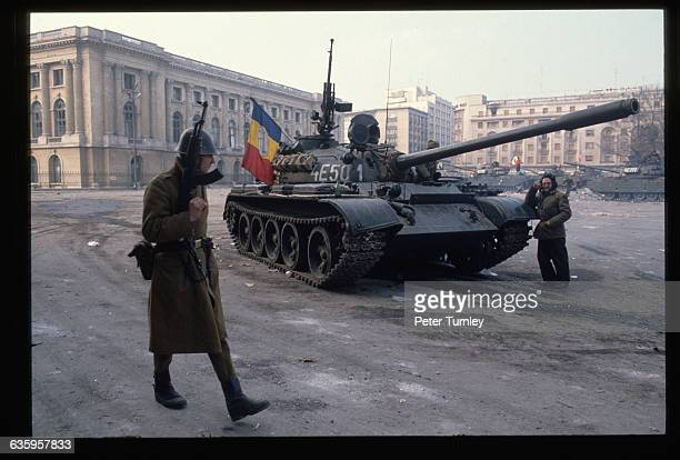 Soldiers keep watch and man tanks in a square in Bucharest during the revolution of December 1989