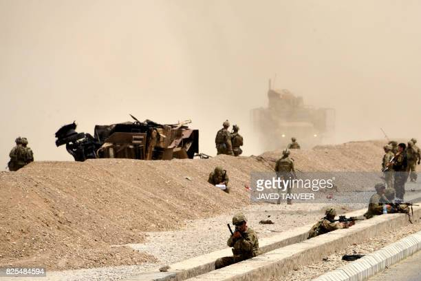 US soldiers keep watch near the wreckage of their vehicle at the site of a Taliban suicide attack in Kandahar on August 2 2017 A Taliban suicide...