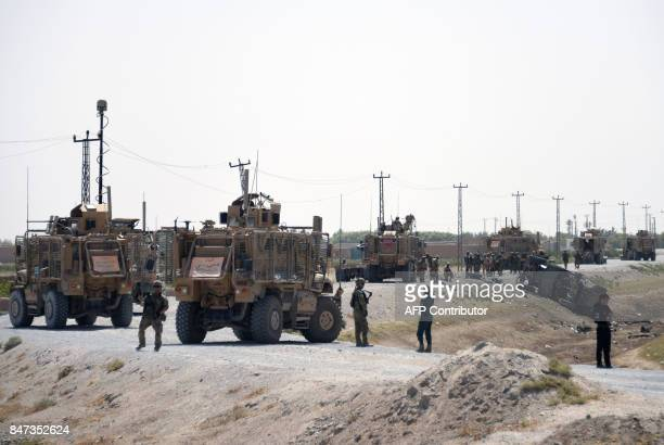 NATO soldiers keep watch near the wreckage of their vehicle at the site of a Taliban suicide attack in Kandahar on September 15 2017 A suicide...
