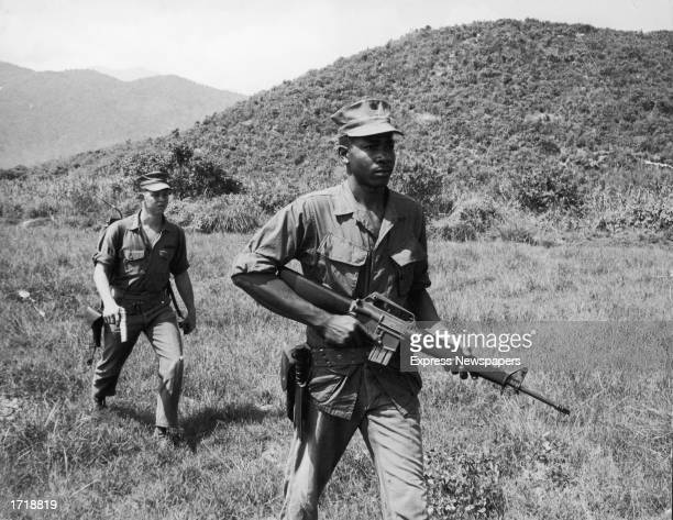 Soldiers Lance Corporal Murphy and Sergeant Paige patrol a jungle area carrying a rifle and a pistol during the Vietnam War 1960s