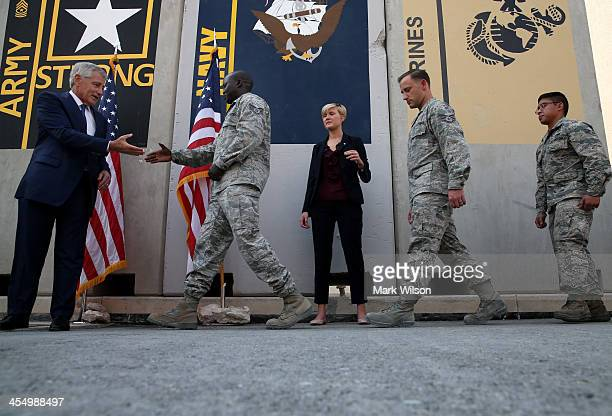Soldiers line up to have their picture taken with US Secretary of Defense Chuck Hagel on December 10 2013 at Al Udeid Airbase west of Doha Qatar...