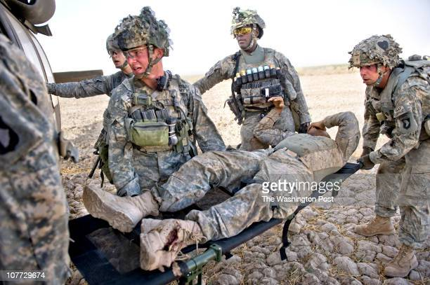 US soldiers load a soldier with foot trauma from an IED blast into the Task Force Shadow Medivac helicopter to be transported to Kandahar Airbase...