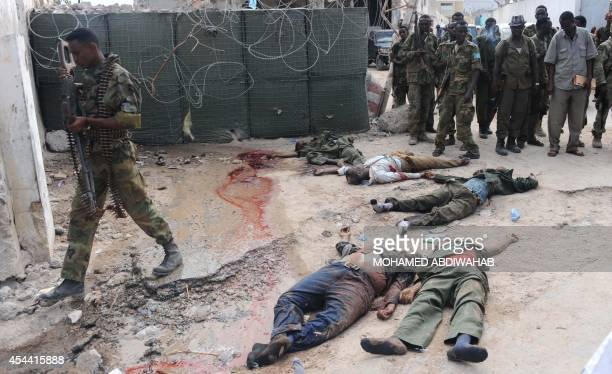 Soldiers look at the bodies of six alleged Shebab rebels on August 31 2014 in a street of Mogadishu after they carried out a major car bomb and gun...