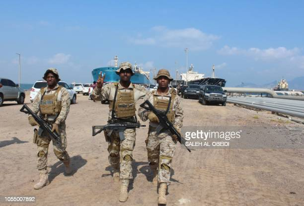 Soldiers loyal to Saudiled coalition forces gesture as they guard ships docked in the southern Yemeni port of Aden on October 29 2018 Saudi...