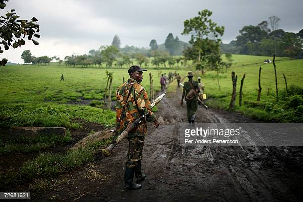 Soldiers loyal to the elusive rebel leader General Laurent Nkunda walk armed on a field after a training exercise on October 2 2006 in Kilolirwe...