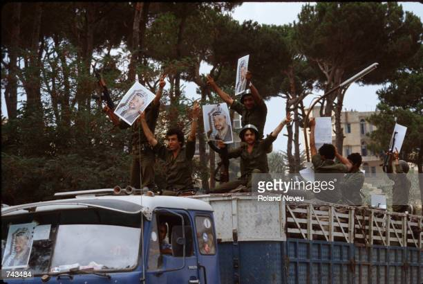Soldiers loyal to Yasir Arafat hold up his picture as they ride a truck August 27, 1982 exiting Beirut, Lebanon. PLO and Syrian forces evacuate the...