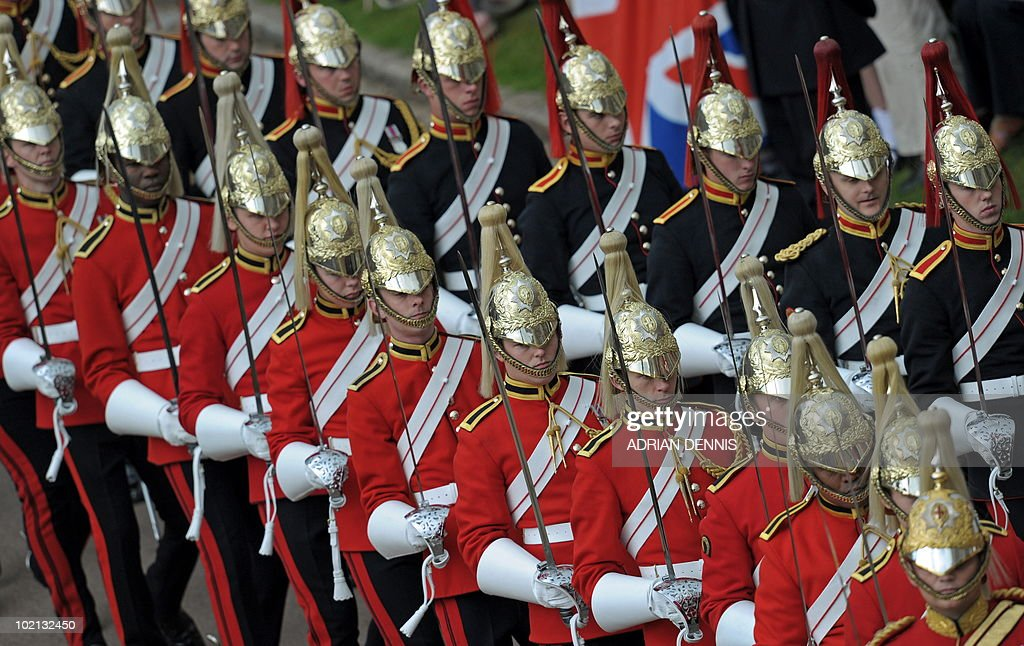 Soldiers march ahead of Britain's Queen Elizabeth II in a procession, to attend The Order of the Garter Service, at St George's Chapel in Windsor Castle, Windsor, southern England on June 14, 2010. The Order of the Garter is the most senior and the oldest British Order of Chivalry and was founded by Edward III in 1348. The patron saint of the Order is St George (patron saint of soldiers and also of England) and the spiritual home of the Order is St George's Chapel, Windsor. Every knight is required to display a banner of his arms in the Chapel, together with a helmet, crest and sword and an enamelled stallplate. These 'achievements' are taken down on the knight's death and the insignia are returned to the Sovereign. The stallplates remain as a memorial and these now form one of the finest collections of heraldry in the world.