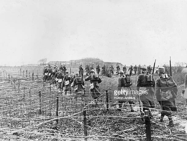 Soldiers marching past land covered by barbed wire during WW I