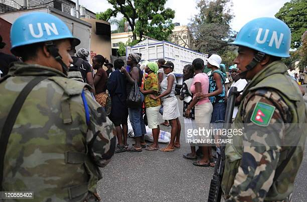 Soldiers monitor food distribution on February 11, 2010 to women in the town of Petion-ville a suburb of Port au Prince. European forces will provide...