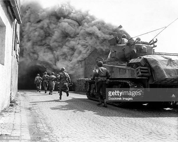Soldiers move through a smoke filled street, Wernberg, Germany.