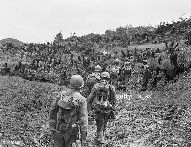 Soldiers move up to take positions on the lightest ridge on Okinawa near the village of Naha.