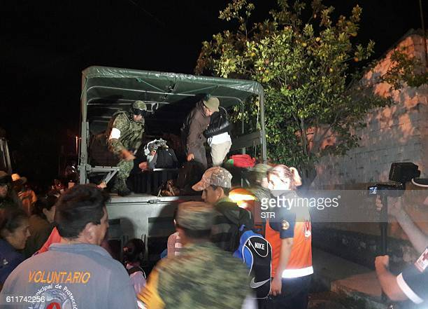 Soldiers municipal workers and volunteers help residents evacuate their homes in Comala Colima State Mexico on October 1 2016 early morning Some 400...