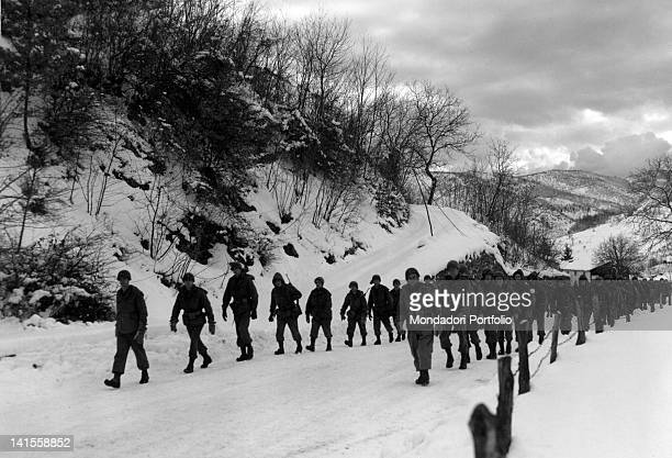 US soldiers of 339th Infantry Regiment during a training march on a snowy road Campo Tizzoro January 1945