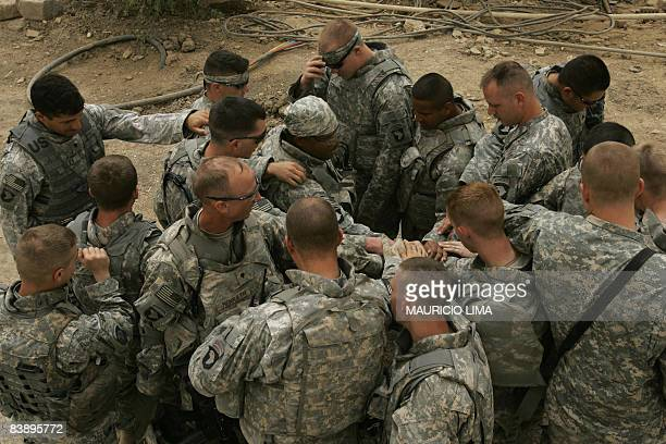 Soldiers of 3rd Battalion, 320th Field Artillery Regiment, hold hands hands as they pray before leave an Iraqi army compound for a mission, in...