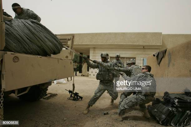US soldiers of 3rd Battalion 320th Field Artillery Regiment unload razor wire as part of security materials delivered to set up checkpoints by new...