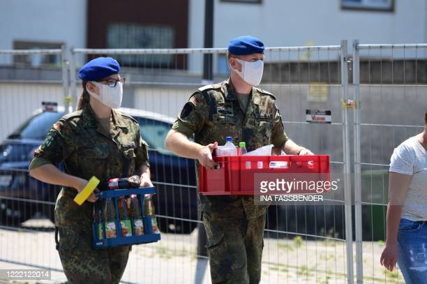 Soldiers of a mobile testing unit of the German Red Cross and the German army prepare for collecting Covid-19 tests from employees of Toennies...