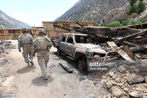 Soldiers of Charlie Company the US Army's 10th Mountain Division pass by rubble and the remnants of a truck evidence of fighting with Taliban...