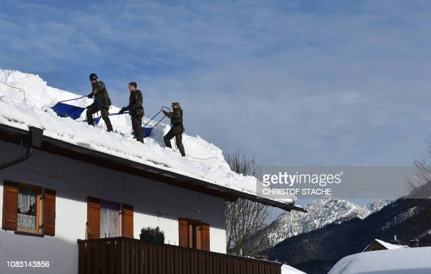 Soldiers of German army Bundeswehr remove snow from a rooftop in the small Bavarian village of Kruen near Garmisch-Partenkirchen, southern Germany,...