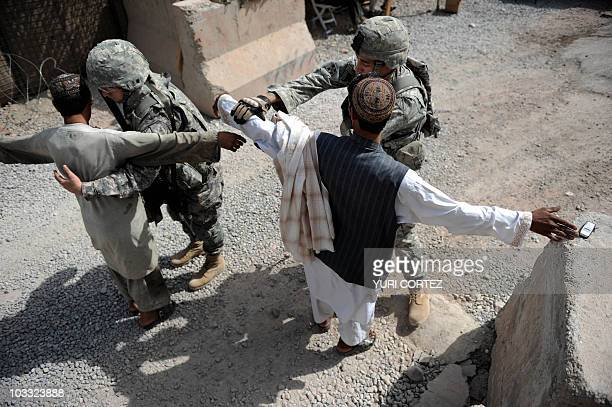 US soldiers of HHC 2508th PIR 4th BTC 82nd Airborne Division search an Afghan pedestrian at a checkpoint in The Arghandab Valley on August 9 2010 A...