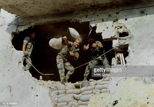 Soldiers of Lebanese army throw sandbag through the hole of a building in order to demolish barricades and fortifications in the Palestinian camp of...