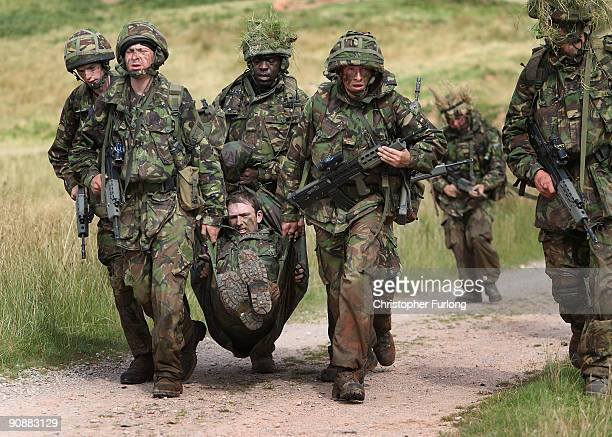 Soldiers of London's only territorial army infantry unit The London Regiment evacuate a mock casualty as they take part in a live firing exercise in...