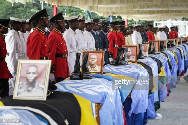 Soldiers of Tanzania People's Defence Force stand beside the coffins of Tanzanian peacekeeperes who were killed by by suspected Ugandan rebels at the...