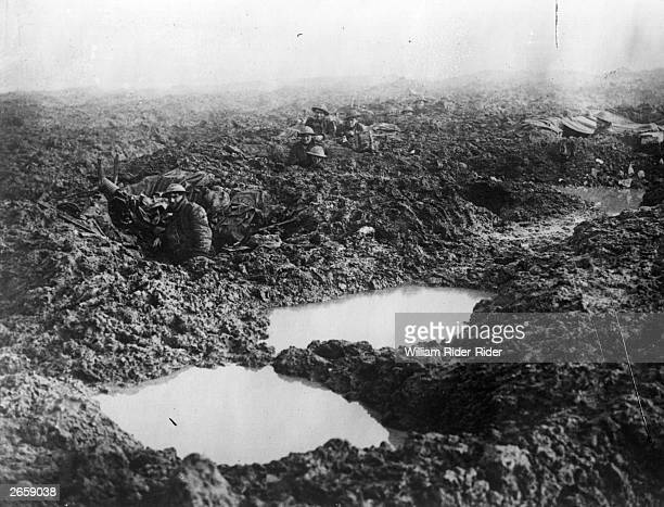 Soldiers of the 16th Canadian machine gun regiment using shell holes as makeshift defences at Passchendaele Ridge