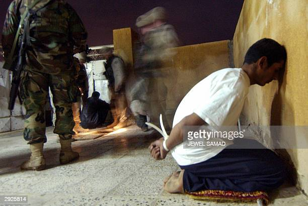 Soldiers of the 1st Battalion, 22nd Infantry Regiment of the 4th Infantry Division conduct a search as an Iraqi detainee sits tied up during a raid...