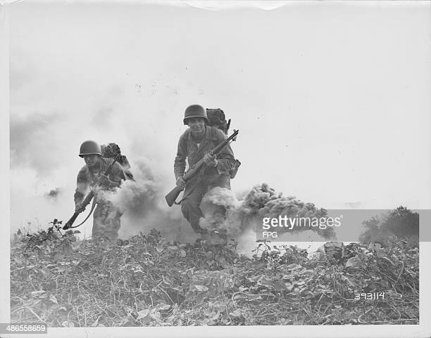 US soldiers of the 29th Infantry moving under smoke cover in field exercises during World War Two Okinawa Japan circa 19411945