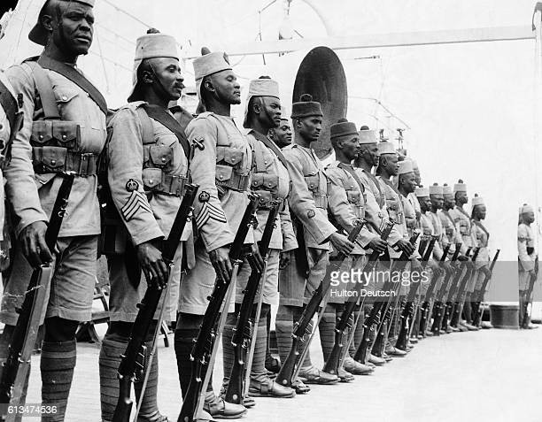 Soldiers of the 3rd Nigerian Regiment of the Royal West African Force stand to attention during a parade on board their ship the SS Accra on their...