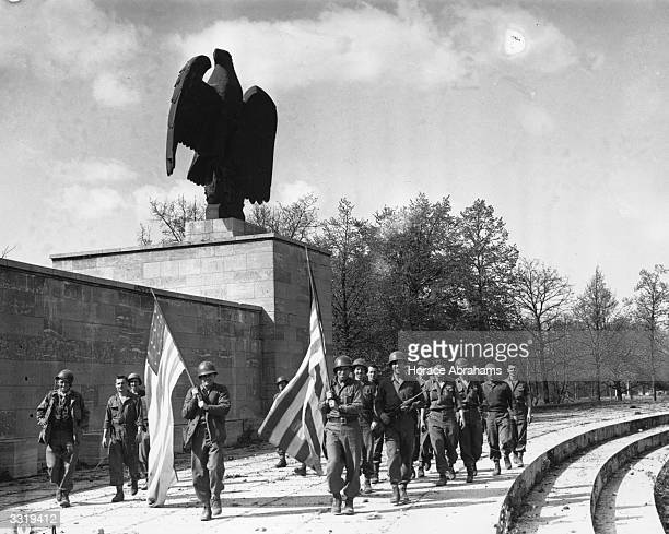 US soldiers of the 45th Division carrying US flags past a stone German eagle in the Luitpold Arena Nuremberg on VDay Now weedcovered Hitler used the...