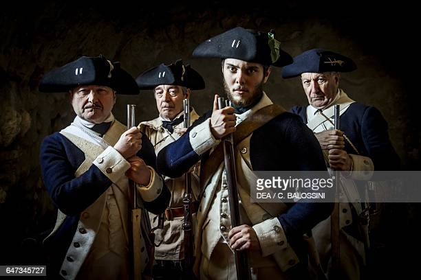 Soldiers of the 4th Massachusetts Regiment wearing tricorn hats blue uniforms and holding muzzleloading flintlock rifles American Revolutionary War...