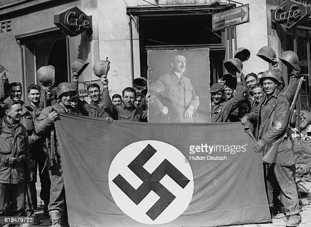 Soldiers of the 7th US division seen with a Nazi flag and a portrait of the Fuehrer Saarbrucken the capital of the Saar falls without a battle to the...