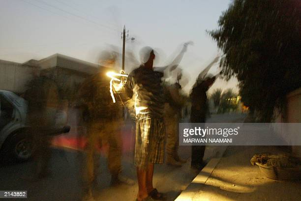 Soldiers of the 82nd Airborne Division on patrol search and arrest two Iraqi men, whom they later released, in northwest Baghdad 29 June 2003 during...