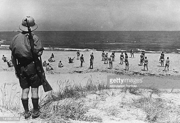 Soldiers of the Africa Korps bathing on a beach on the coast of Cyrenaica under the eyes of an Italian sentryáLibya May 1941