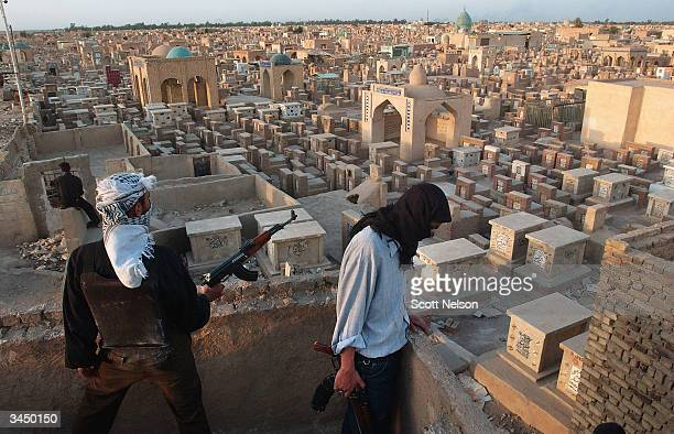 Soldiers of the AlMedhi Army stand guard at their defensive position overlooking the Najaf cemetary April 20 2004 inside the holy Iraqi Shia city of...