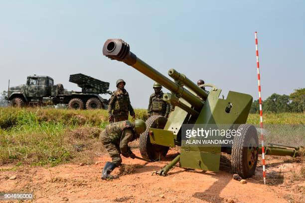 Soldiers of the Armed Forces of the Democratic Republic of the Congo install a mobile artillery piece next to a mobile multiple rocket launcher in...