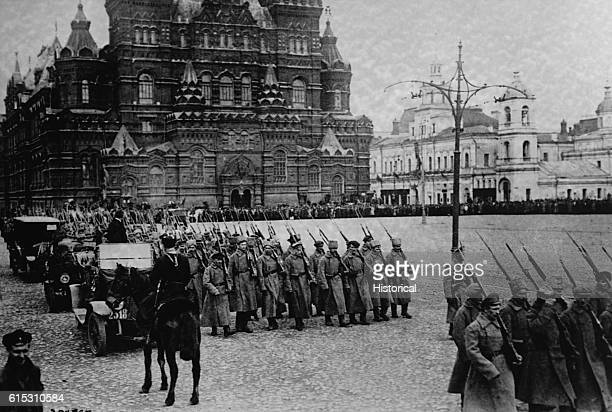 Soldiers of the Bolshevik Army march through Red Square near the Kremlin In the foreground is a mounted Cossack officer ca 1917