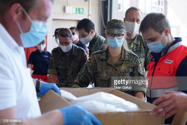 Soldiers of the Bundeswehr and members of the German Red Cross stock up on PPE supplies at a fire department in the village of St. Vit before heading...