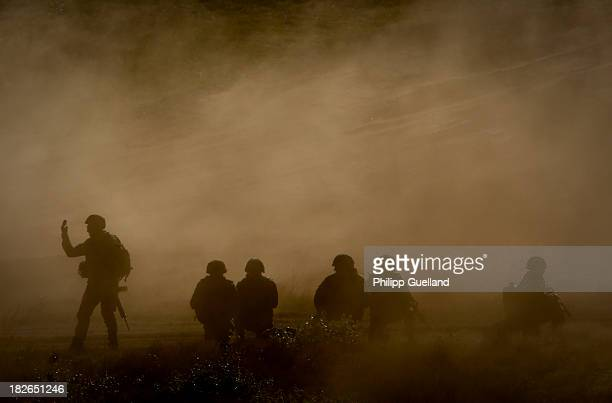 Soldiers of the Bundeswehr are silhouetted during the annual military exercises held for the media at the Bergen military training grounds on October...
