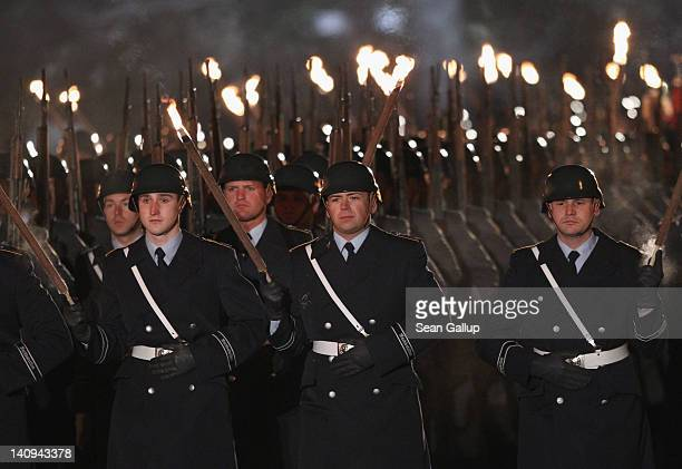 Soldiers of the Bundeswehr bear torches as they arrive for the Zapfenstreich or taps farewell ceremony for former German President Christian Wulff at...