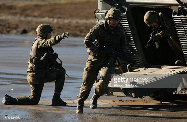 Soldiers of the Bundeswehr dismount from an armoured personnel carrier during the annual military exercises held for the media at the Bergen military...