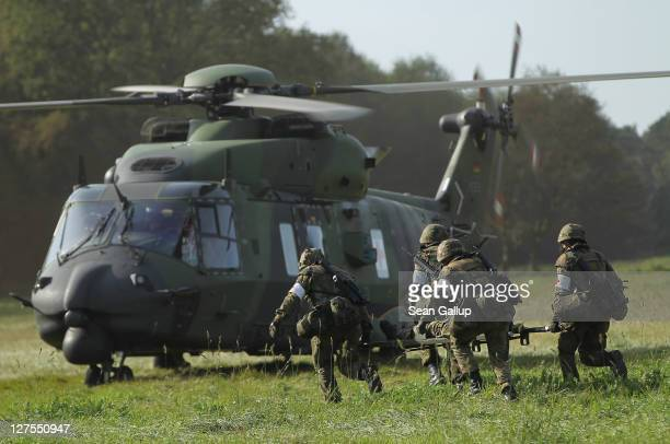 Soldiers of the Bundeswehr German armed forces evacuate a comrade pretending to be wounded to a medivac NH 90 helicopter during military exercises on...