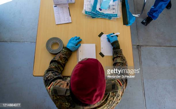 Soldiers of the Bundeswehr Germany's armed forces receive people with possible Covid19 symptoms at the Heeresinstandsetzungslogistik Werk on March 25...