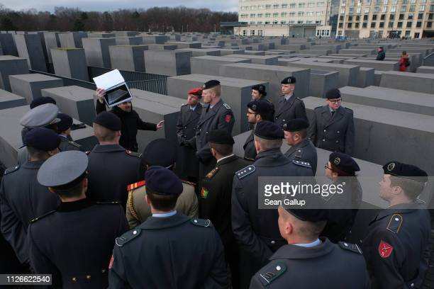 Soldiers of the Bundeswehr the German armed forces as well as a few soldiers from other nations listen to a guide's presentation at the Memorial to...