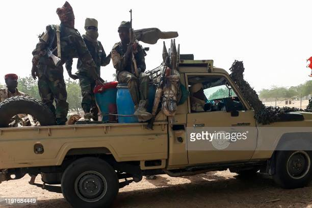 Soldiers of the Chad Army sit on the back of a Land Cruiser at the Koundoul market, 25 km from N'Djamena, on January 3 upon their return after a...